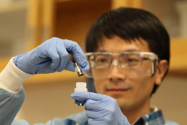 Jianchao Ye, a researcher at Lawrence Livermore National Laboratory, shows off an improved lithium ion battery. Credit: Julie Russell/LLNL