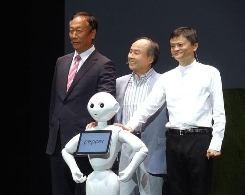 From left to right, Foxconn Technology Group CEO Terry Gou, SoftBank CEO Masayoshi Son and Alibaba founder Jack Ma pose with household communications robot Pepper at Maihama, Japan, June 18, 2015.