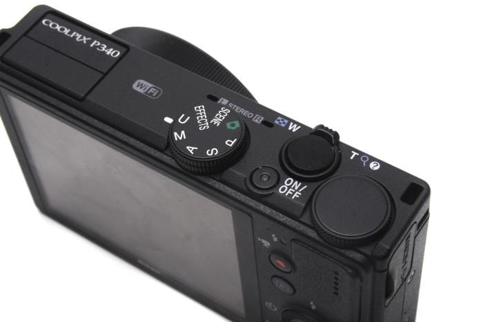 The top view shows the concealed flash on the left, the mode dial, and the dial that can be used to change shutter speed in manual mode.